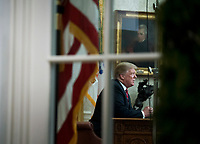 President Donald Trump is seen through the window of the Oval Office as he delivers a primetime address on the government shutdown and his funding request for over $5 billion for a southern border wall, at the White House in Washington, D.C. Photo Credit: Kevin Dietsch/CNP/AdMedia