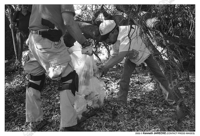 Civil Homeland Defense volunteers clean-up an illegal alien hold-up area on the Fourth of July. Cochise County, Arizona, July 2003.