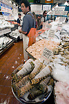 A fish monger at Pike Place Fish Company stands by fish, shellfish, shrimp and crabs for sale at Pike Place Market in Seattle. For over a century a century, the Pike Place Market, has become a city institution and a national attraction, bringing in over a million tourists a year. .Jim Bryant Photo. ©2010. ALL RIGHTS RESERVED.