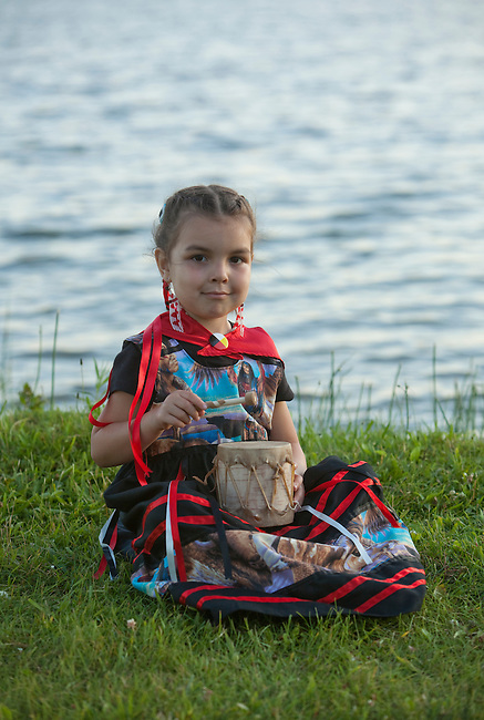 Ojibwe child uses a traditionally made birchbark tom tom drum covered with rawhide next to a lake, Midland Ontario Canada
