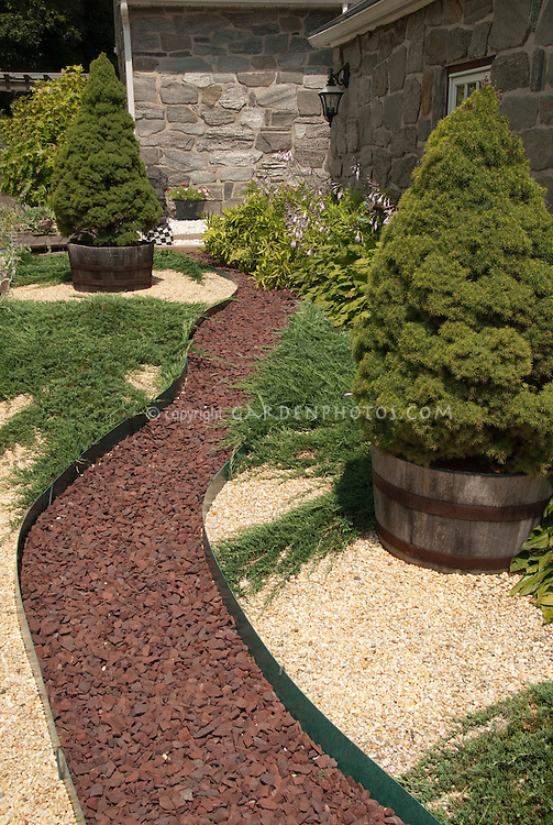 Path to house made of stone pebbles next to evergreen trees in container pots, with contrasting colored stone mulch, stone house