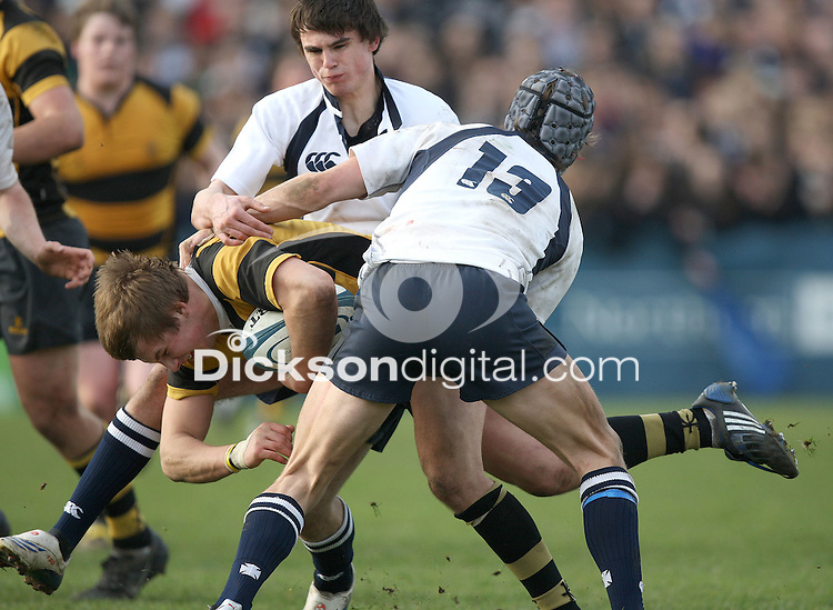 RBAI skipper Darryl Maxwell is tackled by Michael Allen and David Martin during the Northern Bank Schools Cup Final against Methody at Ravenhill, Belfast. Mandatory Credit - John Dickson