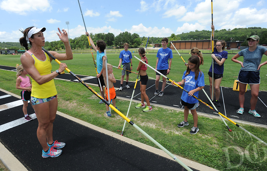 NWA Democrat-Gazette/ANDY SHUPE<br /> April Steiner Bennett (left), a former Arkansas and Olympic pole vaulter, works with campers Friday, June 16, 2017, during instruction for pole vaulters at Ramay Junior High School in Fayetteville. Steiner Bennett and Stacy Dragila, a former Olympic pole vaulter and 2000 Olympic gold medalist, were on hand for two days of intensive instruction for vaulters from elementary to high school.