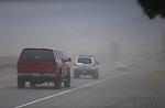 Traffic on Kimmerling Road moves through billowing dust Friday afternoon. Dozens of homes and businesses with roof, fence and tree damage are seen in the Ranchos area of  Gardnerville, Nev., on Friday, Feb. 6, 2015. A powerful wind and rain storm will continue to move through the area over the next few days. <br /> Photo by Cathleen Allison
