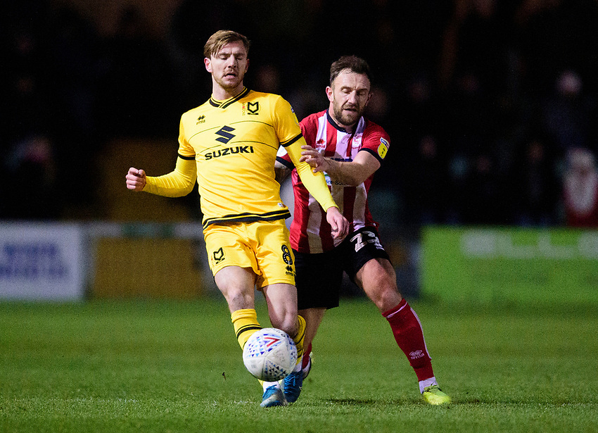 Milton Keynes Dons' Alex Gilbey shields the ball from Lincoln City's Neal Eardley<br /> <br /> Photographer Andrew Vaughan/CameraSport<br /> <br /> The EFL Sky Bet League One - Lincoln City v Milton Keynes Dons - Tuesday 11th February 2020 - LNER Stadium - Lincoln<br /> <br /> World Copyright © 2020 CameraSport. All rights reserved. 43 Linden Ave. Countesthorpe. Leicester. England. LE8 5PG - Tel: +44 (0) 116 277 4147 - admin@camerasport.com - www.camerasport.com