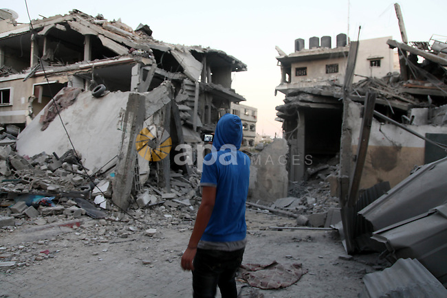 A Palestinian man stands looking at destroyed buildings in the Jabalia refugee camp in the northern Gaza Strip on August 8, 2014. Israel launched air strikes across the Gaza Strip on Friday in response to Palestinian rockets fired after Egyptian-mediated talks failed to extend a 72-hour truce in the month-long war. Photo by Ezz Zanoun