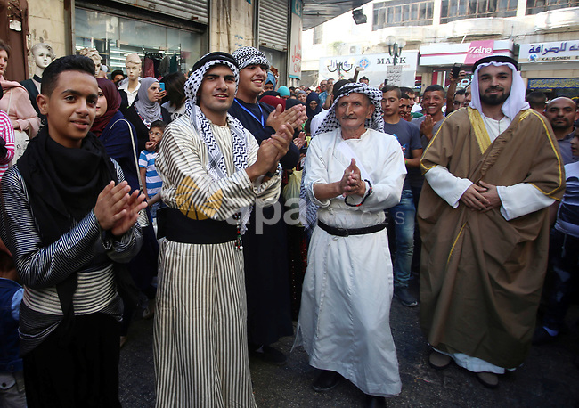 Palestinian band members wear a traditional costumes, perform during a festival marking Traditional Palestinian Dress Day, in the West Bank city of Nablus on August 22, 2017. Photo by Ayman Ameen