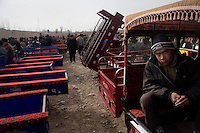 A teenage boy sits in the back of small work vehicles for sale at a market outside Kashgar, Xinjiang, China.