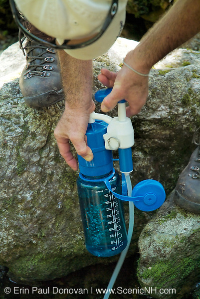 A hiker uses a water filtering system on Meader Ridge Trail in the White Mountains, New Hampshire USA during the spring months.