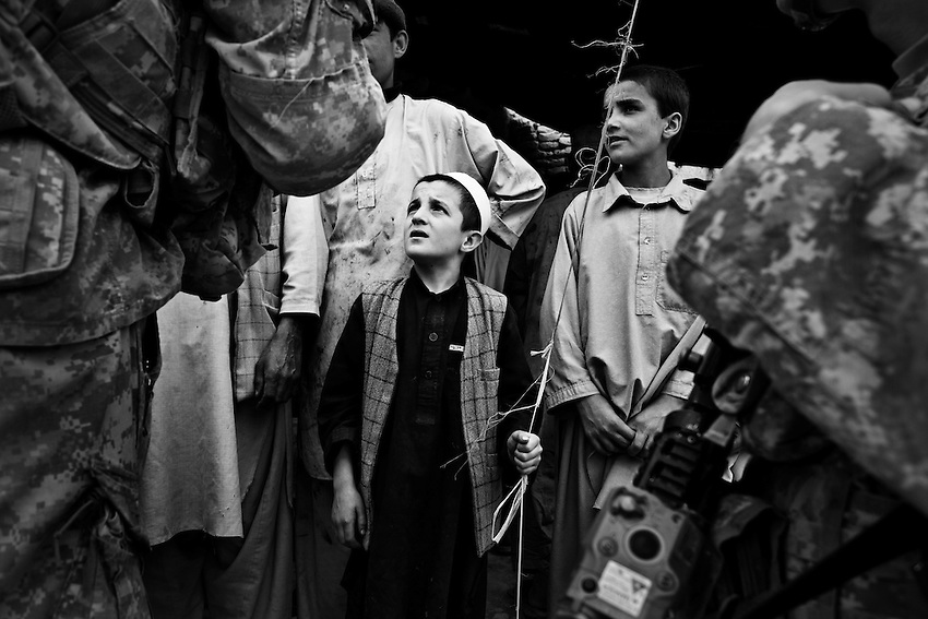 Afghan boys wait while members of 2nd Platoon, Bravo Company, 1-32 Infantry, 3rd Brigade, 10th Mountain Division, hand out toys in the bazaar area of Charkh, Afghanistan, Thursday, May 7, 2009.