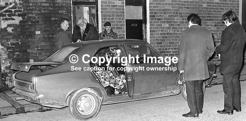 Soldier stands guard as detectives examine car in which the body of Stephen Kernan, 56 years, taxi driver, Roman Catholic, from Newtownabbey, N Ireland, was found in a car in the loyalist Shankill Road area of Belfast on 1st March 1973. The weapon used in the killing had been stolen from the RUC and it was later recovered in a security force search in Sandy Row, another loyalist area of Belfast. 1973030&sect;0116.<br />
