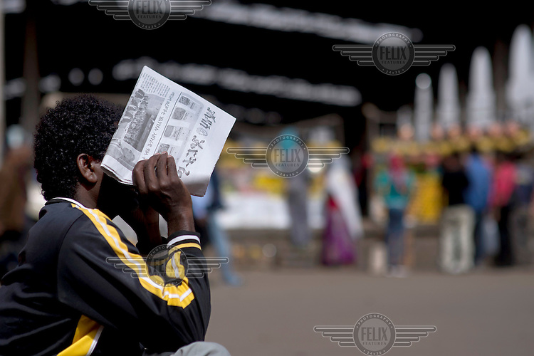 A man with a newspaper in a city market.