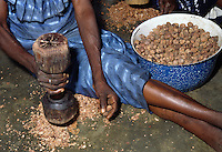 Woman crushing shea nuts for  processing