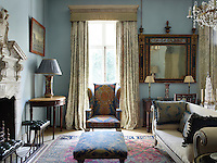 The sitting room is decorated in a cool blue with traditional furnishings. At the window are curtains in Hardwick Green by Robert Kime for Chelsea Textiles.