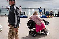 Elderly disabled woman riding an electric buggy on the quay with the beach and sea in the background.??Looe, Cornwall, UK??Date Taken: 05/08/10??Commissioned by: Paul