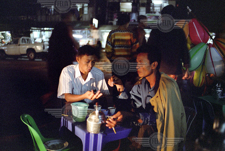 Two men sit and drink tea and smoke at a tea stall in downtown Rangoon (Yangon) close to the famous Shwedagon Pagoda (also known as the Great Dagon Pagoda). ..