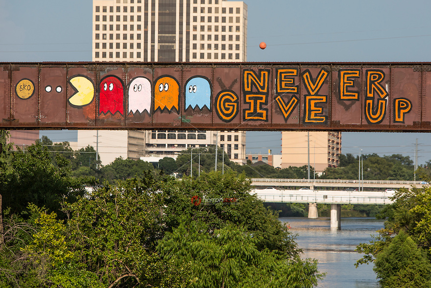 """Never Give Up"" Pac-Man is a famous inspirational graffiti painting on the Austin Railroad Graffiti Bridge over Lady Bird Lake in Austin, Texas."