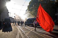 Un manifestante sventola una enorme bandiera rossa davanti la polizia.A protestor waves a giant red flag in front of anti-riot police