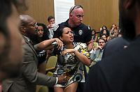 After being warned several times, a woman is escorted out of the meeting by Charlottesville police during the Charlottesville City Council meeting Monday night in Charlottesville, Va. The meeting was shut down then later reinstated to here the grievances of the protestors. Photo/Andrew Shurtleff