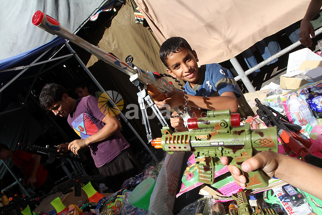 Palestinian boys play with a toy at an outdoor market during preparations for Eid El-Fitr holiday, which marks the end of the holy Muslim fasting month of Ramadan, in Gaza City on Sept. 8, 2010 . Photo by Ashraf Amra