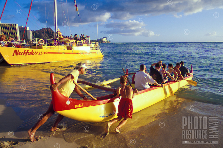 Launching an outrigger canoe off Waikiki with Diamond Head in the background