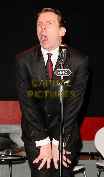 "ROBIN SEBASTIAN.Stage photocall for the new play ""Stop Messing About"" at the Leicester Square Theatre, London, England, .April 16th 2009..on stage performing acting scene half length funny face mouth open hands eye red tie microphone stand black suit BBC winking costume.CAP/CAN.©Can Nguyen/Capital Pictures"