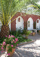 Red trellis arches frame alcoves in the courtyard