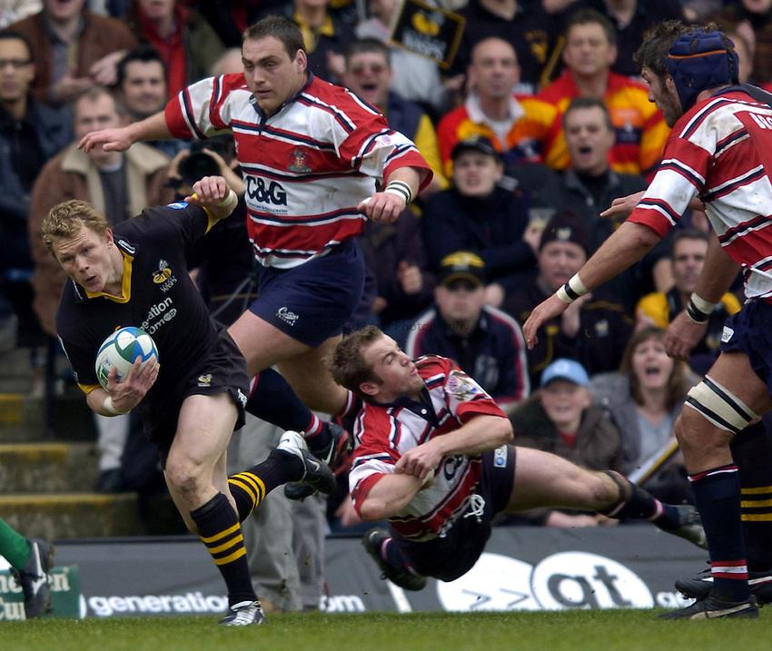 Photo: Richard Lane..London Wasps v Gloucester. Heineken Cup Quarter Final. 11/04/2004..Josh Lewsey breaks James Simpson-Daniel's tackle.
