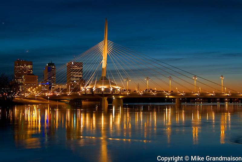 Esplanade Riel Bridge, the Red River and the Winnipeg skyline at dusk<br /> Winnipeg<br /> Manitoba<br /> Canada