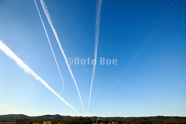 airplane vapor trails converging and one heading towards a other direction