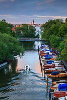 Träbåtar  vid långa bryggor i lummiga Pålsundskanalen mellan Långholmen och Södermalm i Stockholm
