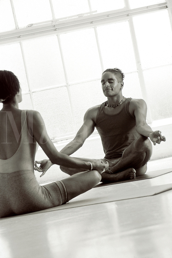 Man and woman in lotus position meditating.
