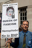 London, England, 2 July 2011, Pride London 2011 celebrations in Central London. Gay rights activist Peter Tatchell with a poster of Nick Griffin, BNP, wearing gay eyeshadow and swastika earrings. Photo credit: Bettina Strenske