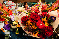 A woman helps sell flowers at her family's flower stand in downtown Charlotte, NC. The family grows flowers on their North Carolina farm, then sells the fresh-cut flowers in bulk, as mixed-flower bouquets and as skillfully designed impromptu flower arrangements from under a tent on Tryon Street, a few blocks south of Charlotte's Square in the heart of downtown Charlotte. The florists operate their farmers-market-type flower stand most weekdays during the summer, serving customers who work in uptown Charlotte. In addition to offering shoppers good deals on fresh cut flowers, the flower growers are a bright oasis on Charlotte's city streets.