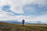 Lone hiker on trail across mountain plataue between Teusjaure and Vakkotavare, Kungsleden trail, Lapland, Sweden