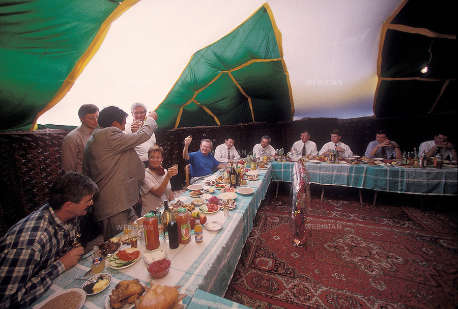 1997..Turkmenistan¿s Oil Minister (from behind) and Unocal 76¿s President, John F. Imle Jr. (facing) give a toast in a traditional yurt in Ashgabat during a meeting with representatives of Turkmenistan¿s government and of the joint venture lead by the US oil company Unocal, to celebrate Turkmenistan¿s independence....Le ministre turkmène du pétrole (de dos) et le président de Unocal 76, John F. Imle Jr. (de face) portent un toast dans une yourte traditionnelle à Ashgabat lors d¿une réunion avec des représentants du gouvernement turkmène et du consortium pétrolier créé par la compagnie pétrolière américaine Unocal, pour célébrer l¿indépendance du Turkménistan.