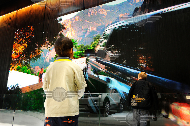 Boys looking at a giant video display for 4x4 Range Rovers behind a wall of water on the Land Rover stand at the Geneva Motor Show. The company is owned by Indian firm Tata.