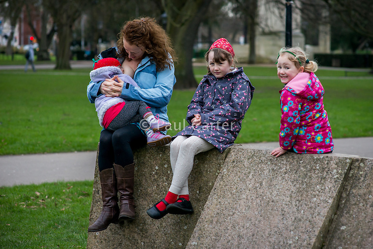 A woman breastfeeds her 20 month old toddler while sitting on a sculpture in a city park on a cold winter's day.  Her older daughters are watching her.<br /> <br /> 07/02/2013<br /> Hampshire, England, UK