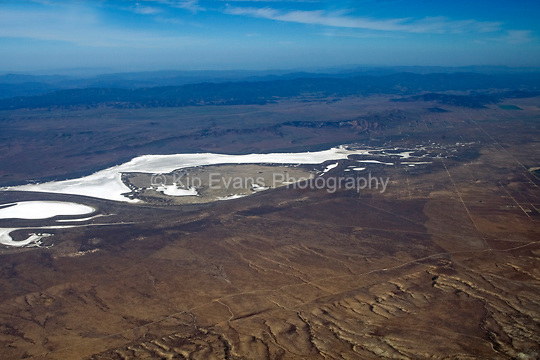 Aerial view of Soda Lake, a shallow, ephemeral, alkali lake, in the Carrizo Plain in southeastern San Luis Obispo County, California. Internal drainage of the Carrizo Plain and the formation of Soda Lake began during Pliocene-Pleistocene time when tectonic deformation associated with the San Andreas Fault defeated a stream that once drained the valley. An originally fresh to brackish water lake probably persisted through much of the Pleistocene during which coastal California was wetter and cooler than now. Diminished Holocene precipitation and a higher evaporation rate led to shrinkage of the ancestral lake and associated increased salinity which set the stage for clay dune formation (wiki 2009)