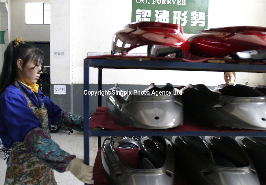 A worker transports body parts used on LPG scooters at the Shanghai Forever Bicycle Factory in Shanghai, China. With the worsening of the city's air pollution due to increased vehicle traffic, the city has banned the sales of gasoline powered scooters in favor of ones that run on cleaner LPG..21-APR-04