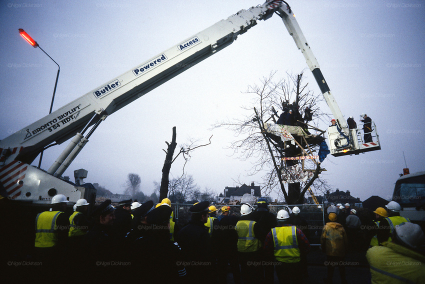Protesters resisting eviction during the Wanstead seige. Road Protest site at George Green, Wanstead, London. The M11 link road protest was the start of a major anti-road protest in Wanstead and Leytonstone, in autumn 1993 opposing the construction of the M11 Link Road. It began with a protest to save the 250-year-old sweet chestnut tree that grew upon George Green. In winter of 1993 dozens of protesters occupied a house on George Green, Wanstead. In the early morning of 7 December 1993, several hundred police and bailiffs arrived to evict the protesters, which took a day hours to carry out.<br />
