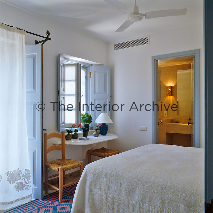 A guest bedroom with a small en-suite bathroom has been decorated simply and perpetuates the blue and white theme of the house