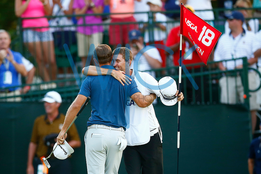 Dustin Johnson hugs his brother Austin Johnson following his first major win on the 18th green during the 2016 U.S. Open in Oakmont, Pennsylvania on Sunday June 19, 2016. (Photo by Jared Wickerham / DKPS)