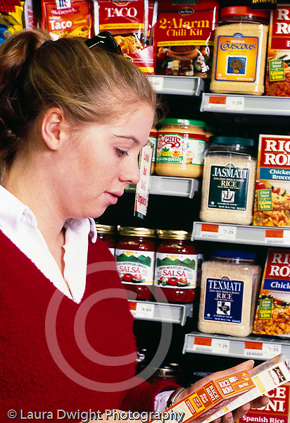 College student female shopping at supermarket, reading label on rice box