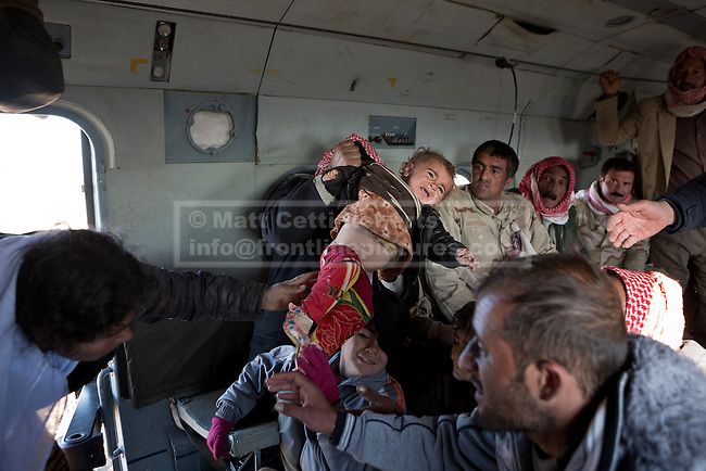11/12/2014. Sinjar Mountains, Iraq. A young Yazidi refugee is handed through the door of Iraqi Air Force Mi-171E Hip helicopter by his or her mother as they are evacuated from Mount Sinjar.<br /> <br /> Although a well publicised exodus of Yazidi refugees took place from Mount Sinjar in August 2014 many still remain on top of the 75 km long ridge-line, with estimates varying from 2000-8000 people, after a corridor kept open by Syrian-Kurdish YPG fighters collapsed during an Islamic State offensive. The mountain is now surrounded on all sides with winter closing in, the only chance of escape or supply being by Iraqi Air Force helicopters.