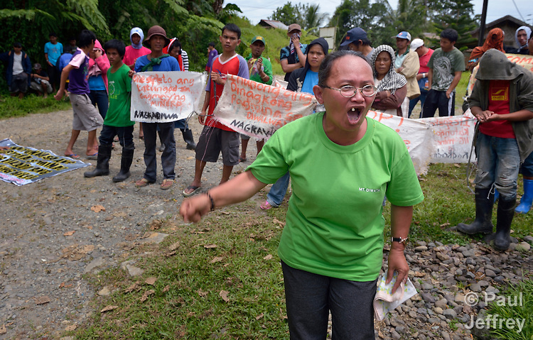 Daylien Elejorde leads a June 4, 2012, rally of small-scale miners in a protest outside the Mt. Diwata offices of the Philippine Mining Development Corporation, a front company for foreign mining companies that seeks to install a large-scale open pit gold mine in the Diwalwal area on the Philippines' southern island of Mindanao. Elejorde, a 43-year old Catholic catechist, operates with her family a small gold mine in the area, also known as Mt. Diwata. She and the other small miners were given a notice to evacuate the area by June 5 or risk being forcibly removed by the military. They have defiantly refused to leave. .