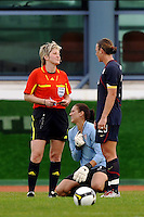 Abby Wambach of the US Women's National Team discusses a foul called on US Goalie Hope Solo (seen holding chest behind) with FIFA referee Christine Beck. Solo was injured on play and had penalty kick called, which she saved. Game was vs Iceland in Vila Real Sto Antonio at the 2010 Algarve Cup.