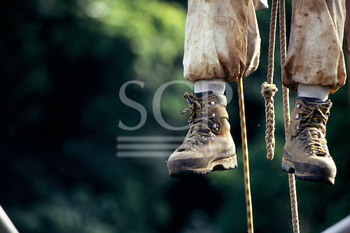 Makande, Gabon. Climber's feet and ropes as he climbs a rainforest tree.