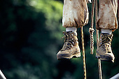 Makande, Gabon. Climber's feet and ropes as he climbs a rainforest tree.