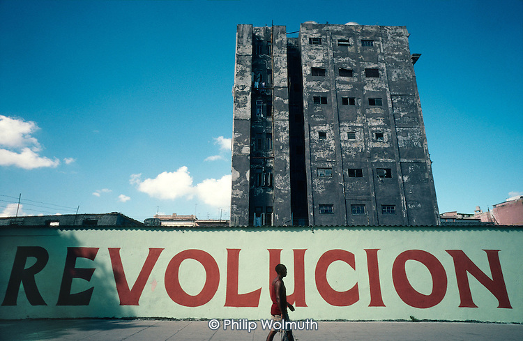 A hoarding celebrates the 1959 revolution in front of a decaying apartment building in Old Havana (Havana Viejo).